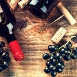 Fijando con la botella de vino rojo, de uva y de corchos Carta de vinos concentrada Foto de archivo libre de regalías
