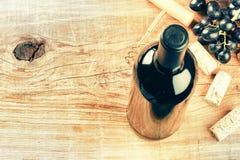 Fijando con la botella de vino rojo, de uva y de corchos con el espacio de la copia Imagen de archivo libre de regalías