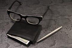 Fije al hombre de negocios Pluma de plata, monedero negro en un viejo fondo Imagen de archivo libre de regalías