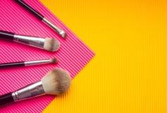 Fije de cepillos del maquillaje contra fondo multicolor Punto de visi?n superior, endecha plana imágenes de archivo libres de regalías
