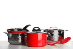 Fije de cookware y de utensilios limpios en la tabla contra el fondo blanco imagenes de archivo