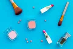 Fije de cosméticos rosados Barra de labios, bulto, sombreador de ojos, perfume cerca de cepillos en la opinión superior del fondo imagen de archivo libre de regalías