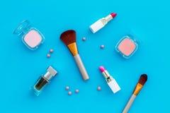 Fije de cosméticos rosados Barra de labios, bulto, sombreador de ojos, perfume cerca de cepillos en la opinión superior del fondo foto de archivo