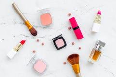 Fije de cosméticos rosados Barra de labios, bulto, sombreador de ojos, perfume cerca de cepillos en la opinión superior del fondo foto de archivo libre de regalías