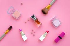 Fije de cosméticos rosados Barra de labios, bulto, sombreador de ojos, perfume cerca de cepillos en la opinión superior del fondo imágenes de archivo libres de regalías
