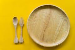 Fije de la bifurcaci?n, de la cuchara y de la madera del plato con el fondo amarillo fotos de archivo libres de regalías