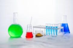 Fije de la cristalería de laboratorio en un fondo blanco Reacción química Experimento químico con el lanzamiento del vapor imagen de archivo