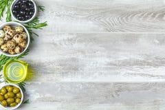 Fije de las aceitunas negras y verdes, huevos de codornices en las placas, aceite de oliva a foto de archivo