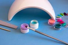 Fije de las herramientas cosméticas para la manicura y la pedicura en un fondo azul imágenes de archivo libres de regalías