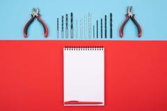 Fije de las herramientas de la trabajo de metalistería con el cuaderno y la pluma en fondo colorido fotografía de archivo