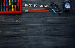 Fije de los efectos de escritorio en el fondo de madera gris Cuentas, vidrios redondos, lápices, despertador De nuevo a escuela,  foto de archivo