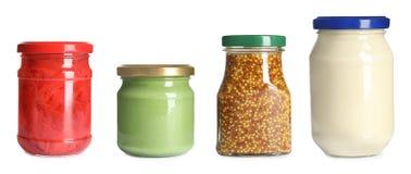 Fije de los tarros de cristal con diversas salsas deliciosas en blanco foto de archivo