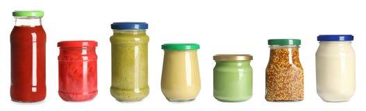 Fije de los tarros de cristal con diversas salsas deliciosas en blanco fotos de archivo libres de regalías