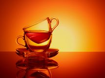 Fije de 2 tazas de cristal para el té Sistema de cristal anaranjado del fondo Té inacabado del concepto imagenes de archivo