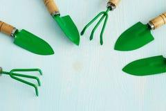 Fije de utensilios de jardinería en un fondo de madera ligero imágenes de archivo libres de regalías