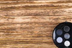 Fije del sombreador de ojos en una caja redonda están en la esquina de un fondo de madera, espacio para sus letras fotos de archivo
