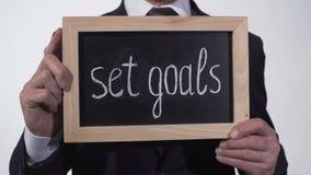 Fije la motivación de las metas escrita en la pizarra en las manos del hombre de negocios, extremidades del éxito almacen de metraje de vídeo