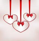 Fije la tarjeta en forma de corazón con el arco de seda para Valentine Day Imagenes de archivo