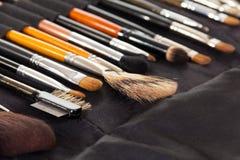 Fije los cepillos cosméticos para el maquillaje en tela de la oscuridad del fondo Foto de archivo