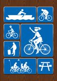 Fije los iconos del barco de rowing, paseo de la familia, bicicleta, zona de tostado Iconos en color azul en fondo de madera Fotos de archivo libres de regalías
