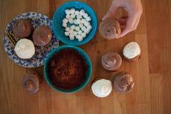 Fije para cocinar, cocinando las magdalenas, los molletes y una placa de los ingredientes para la decoración en la tabla foto de archivo
