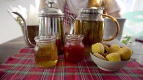Fije para la consumición del té El pote del té, miel, atasco, se apelmaza Mujer con la taza en fondo almacen de metraje de vídeo