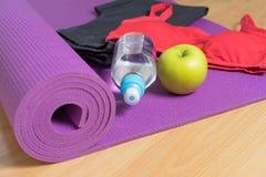 Fije para la práctica de la yoga con la estera de la yoga, botella de agua y ponga verde a Foto de archivo
