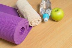 Fije para la práctica de la yoga con la estera, la toalla, la botella de agua y el verde Imagen de archivo libre de regalías