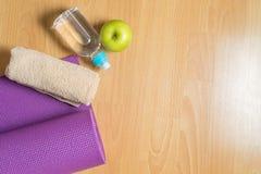 Fije para la práctica de la yoga con la estera, la toalla, la botella de agua y la manzana verde Fotos de archivo libres de regalías