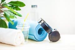 Fije para los deportes Auriculares azules de la toalla de la estera de la yoga y una botella de agua en un fondo ligero que el co fotos de archivo libres de regalías