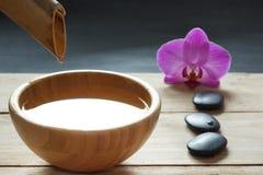 Fije para los procedimientos del balneario, piedras para el masaje caliente y condimentó el agua, reclutada de un tronco de bambú Imagen de archivo