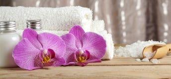 Fije para los tratamientos del balneario con las lociones para la piel, las flores de la orquídea, la sal de baño y las toallas b Fotografía de archivo libre de regalías