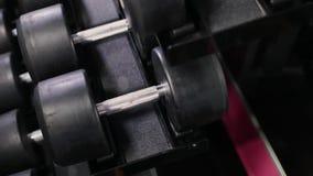 Fije, un estante de pesas de gimnasia de diferente sizen para entrenar, primer almacen de metraje de vídeo