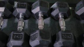 Fije, un estante de pesas de gimnasia de diferente sizen para entrenar, primer metrajes