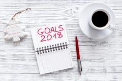 Fije una meta por Año Nuevo Cuaderno cerca de la pluma, de los vidrios y de la taza de café en la opinión superior del fondo de m Imagen de archivo libre de regalías