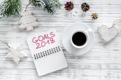Fije una meta por Año Nuevo Cuaderno cerca de la taza de café en la opinión superior del fondo de madera gris Imagen de archivo
