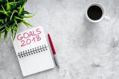 Fije una meta por el Año Nuevo 2018 Cuaderno cerca de la pluma y taza de café en copyspace de piedra gris de la opinión superior  Imagen de archivo