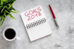 Fije una meta por el Año Nuevo 2018 Cuaderno cerca de la pluma y taza de café en la opinión superior del fondo de piedra gris Imagen de archivo