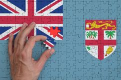 Fiji flag is depicted on a puzzle, which the man`s hand completes to fold.  stock illustration