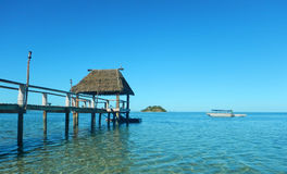 Fiji Island Wharf Lagoon Bungalow. Blue green water island in background Royalty Free Stock Image