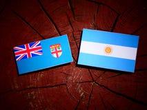 Fijian flag with Argentinian flag on a tree stump isolated Stock Photos