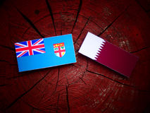 Fijian flag with Qatari flag on a tree stump isolated. Fijian flag with Qatari flag on a tree stump Royalty Free Stock Photo