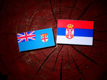 Fijian flag with Serbian flag on a tree stump isolated. Fijian flag with Serbian flag on a tree stump stock photo