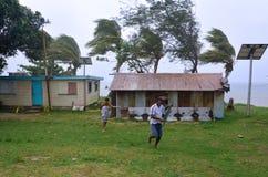 Fijianfolkkörning som får skyddet under en tropiska Cyclon arkivfoto
