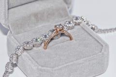 Fijne elegante gouden ring met een diamant en zilveren armband met p Stock Foto's