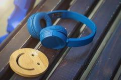 Fijne muziek voor perfecte stemming De draadloze hoofdtelefoons van blauwe kleur liggen op een donkere houten bank Een glimlach H royalty-vrije stock afbeeldingen