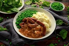 Fijngestampte aardappels en worsten, bangers met uienjus, groene erwten stock afbeeldingen