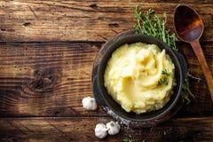 Fijngestampte aardappels, gekookte puree in gietijzerpot op donkere houten rustieke achtergrond, hoogste mening, exemplaarruimte Stock Foto