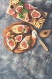 Fikonträd med den skinka-, ost- och rostat brödprosciuttoen med fikonträd på en lantlig bakgrund Den bästa sikten, över huvudet s royaltyfri foto