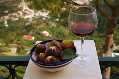Fikonträd och ett exponeringsglas av ett rött vin Arkivfoto